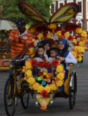 Local tourists on a trishaw joy ride. The trishaws are fitted with huge speakers and belt music across the streets of Melaka