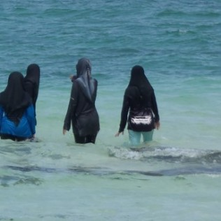 These young ladies enjoying the beach, but not so much the sun.