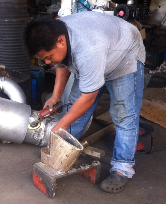 Worker at Tavisuwan Engineering cleaning up the rudder skeg bearing after machining it to size. Notice his safety Crocs..